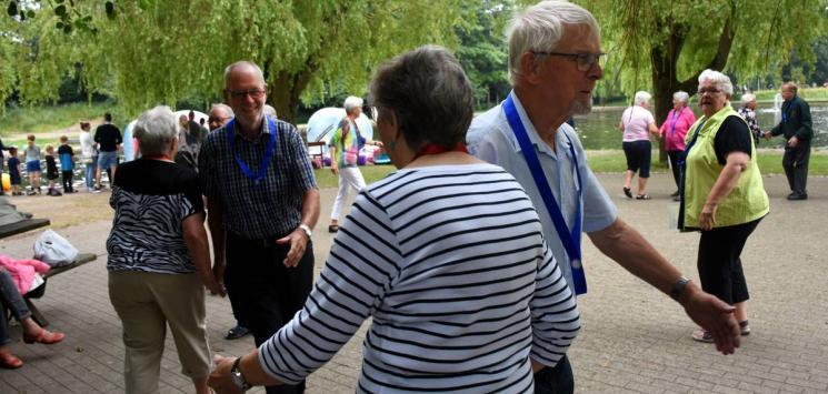 Seniorer danser i Madsby Legepark ved søen